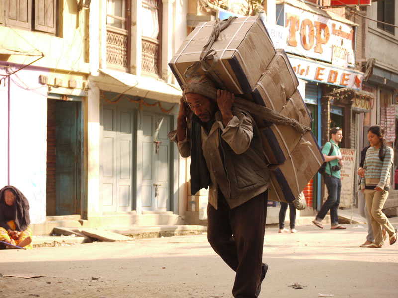 Man carrying a heavy load through the streets of Kathmandu