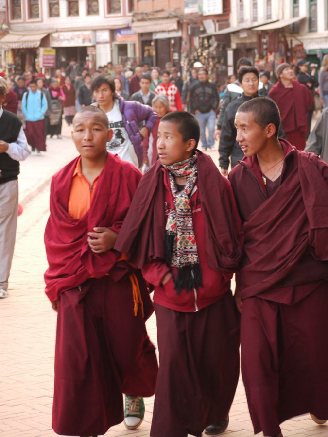 Young monks in marroon robes, circling the Bodhanath Stupa, Nepal