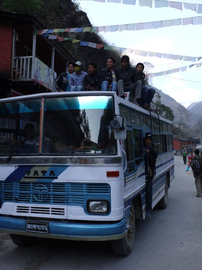 Locals ride the top of the bus through Tatopani in the Kathmandu Valley