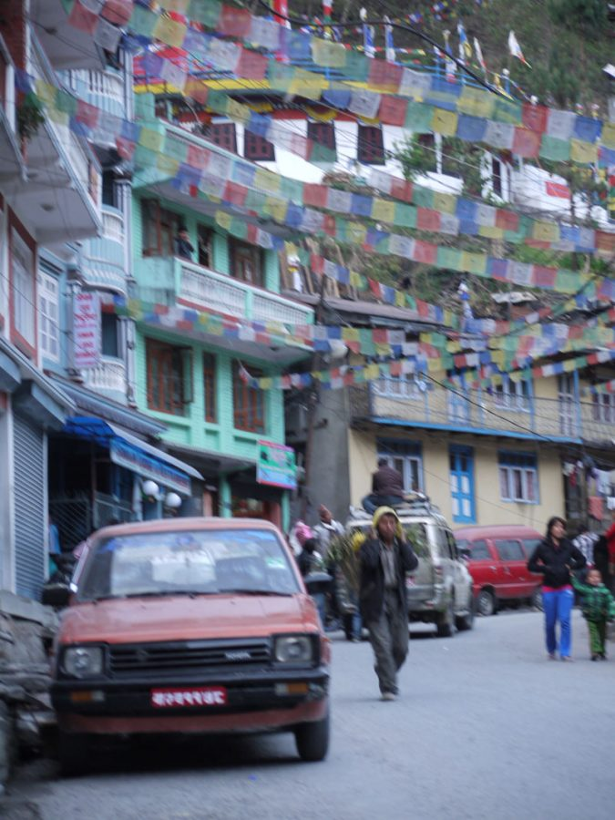 Locals walk along the one street of Tatopani village near the Nepal-Tibet border, Nepal