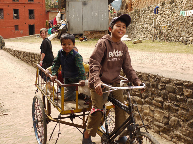 Friendly local kids cycling by in Panauti, Nepal