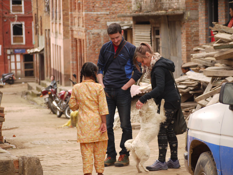 Noelle and Mike playing with someone's pet dog in Panauti, Nepal