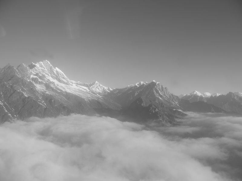 Views of The Himalayas poking out above the clouds during the flight from Kathmandu to Lukla, Nepal