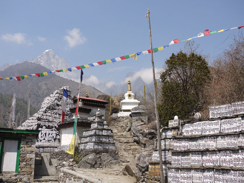 Prayer flags, Buddhit Mantras painted on stones and a stupa on the Eevrest Base Camp Trail