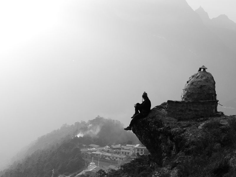 Brian sitting on the edge, looking down at the Tengboche Monastery