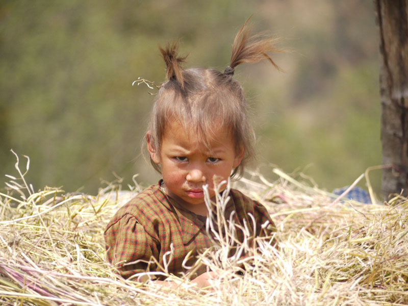 Young girl playing in the straw in the tiny village of Ringmu
