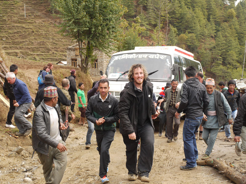Brian with the other men, smiling after they pull bus number three to the top of the hill and it's off to Kathmandu