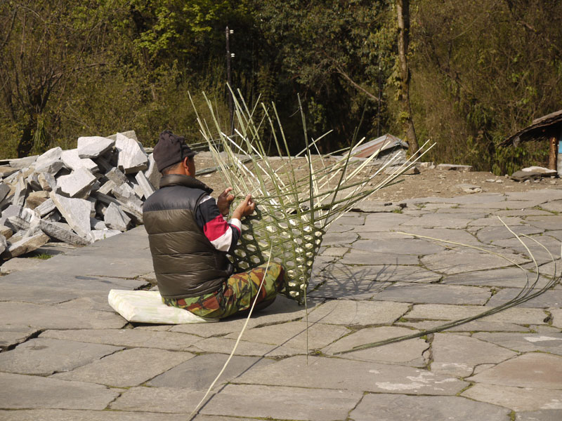 Man in Dobhan weaving a basket from lengths of bamboo