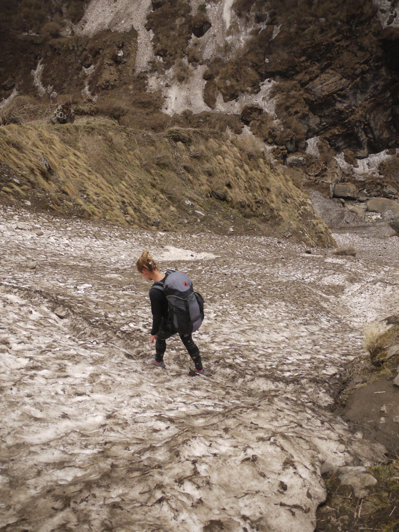 Noelle crossing the narrow, icy path across an avalanche shoot, careful not to put a foot wrong!