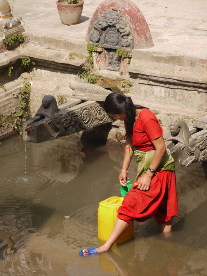Woman at the Manga Hitti gathering water from the stone spouts, Patan