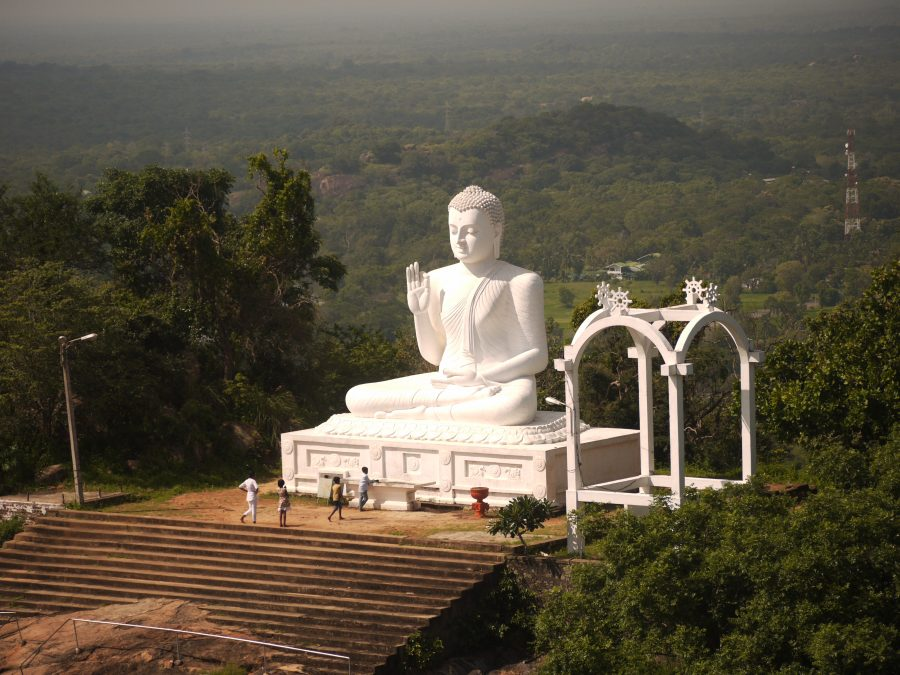 Pilgrims visit the great statue of the Buddha at the sacred mountain of Mihintale, Sri Lanka.