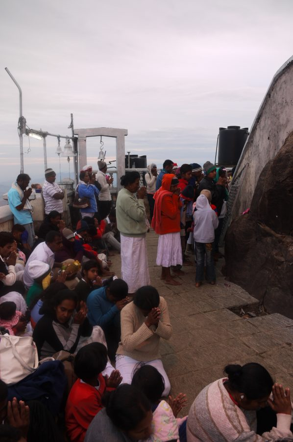 Pilgrims gather to pray at sunrise at the top of Adam's Peak, Sri Lanka