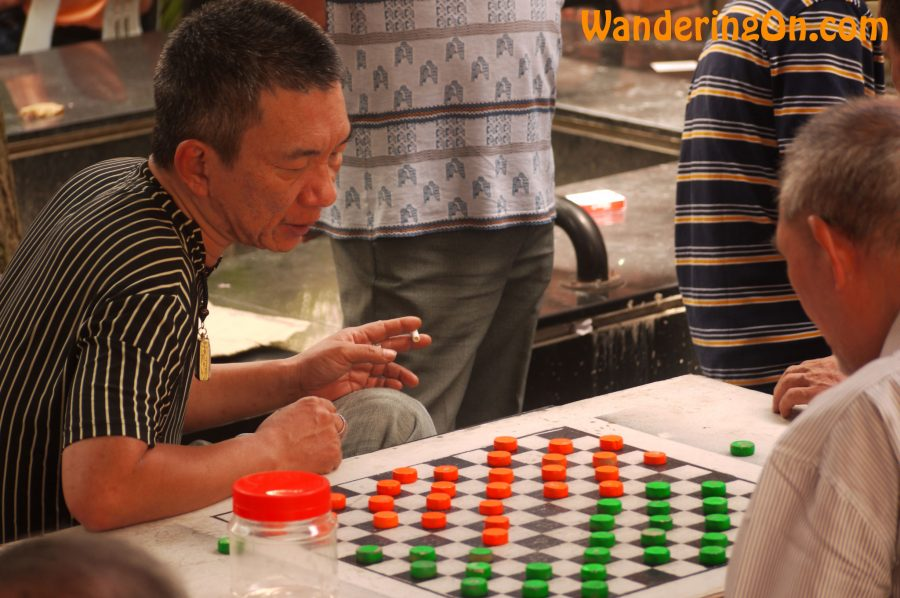 Men playing Chinese checkers in China Town, Singapore