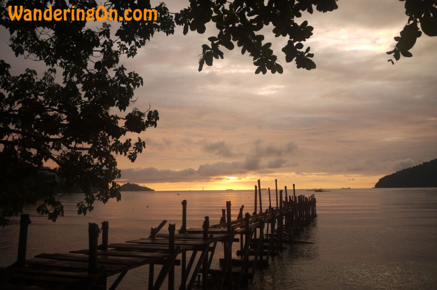 Looking out over a broken pier at the sunset in Bungus Bay, Sumatra, Indonesia
