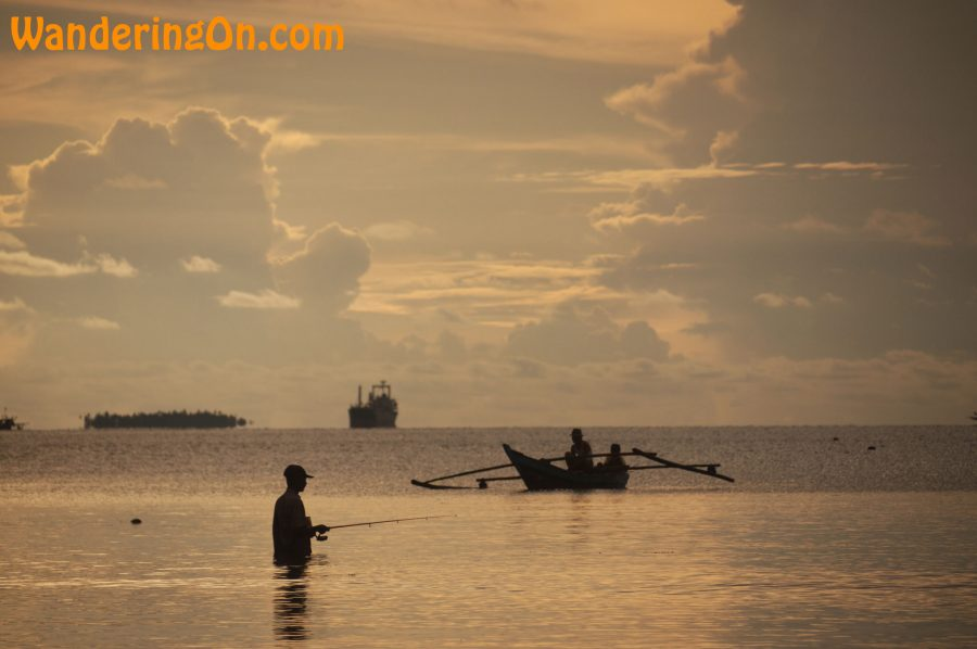 Fisherman and fishing boat silhouetted in Bungus Bay, Sumatra, Indonesia