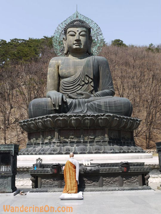 A monk prays in front of a giant statue of the Buddha in Seoraksan National Park, South Korea.