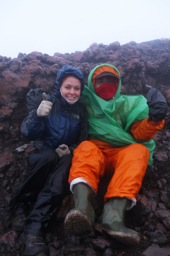 Noelle and Een huddled together on top of Mount Kerinci, Sumatra in awful weather conditions.