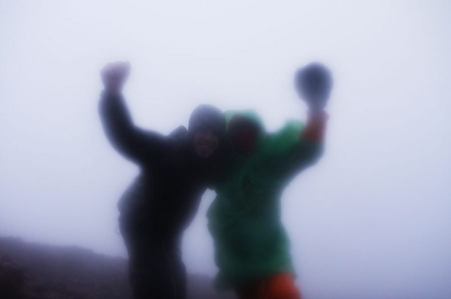 Brian and Een celebrate in the gale force winds and heavy rain after reaching the top of Mount Kerinci, Sumatra