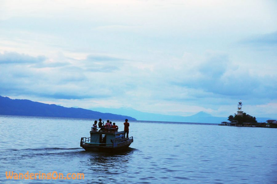 Locals head off across the placid waters of Lake Toba at dusk