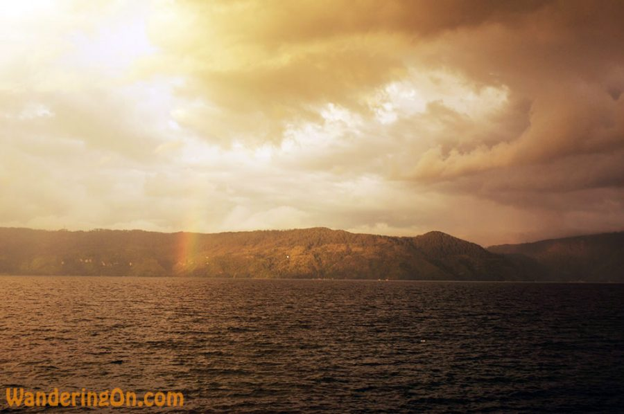 Looking across Danau Toba. Stunning clouds, rainbow and mountains on the far shore
