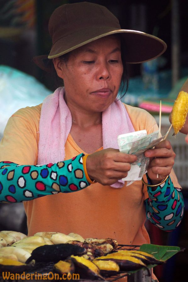 Street vendor counts her money carefully, Bangkok
