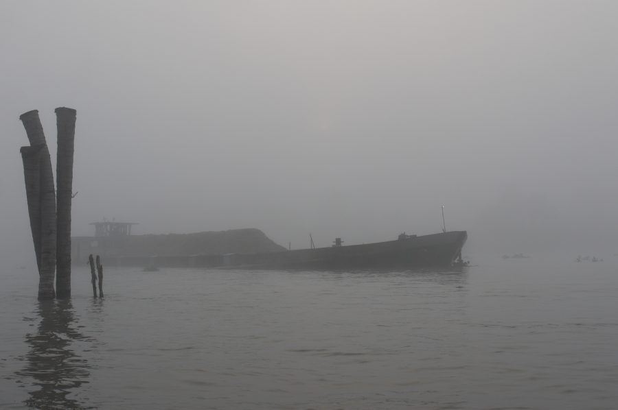 Cargo boat coming through the morning fog before dawn on the Mekong Delta