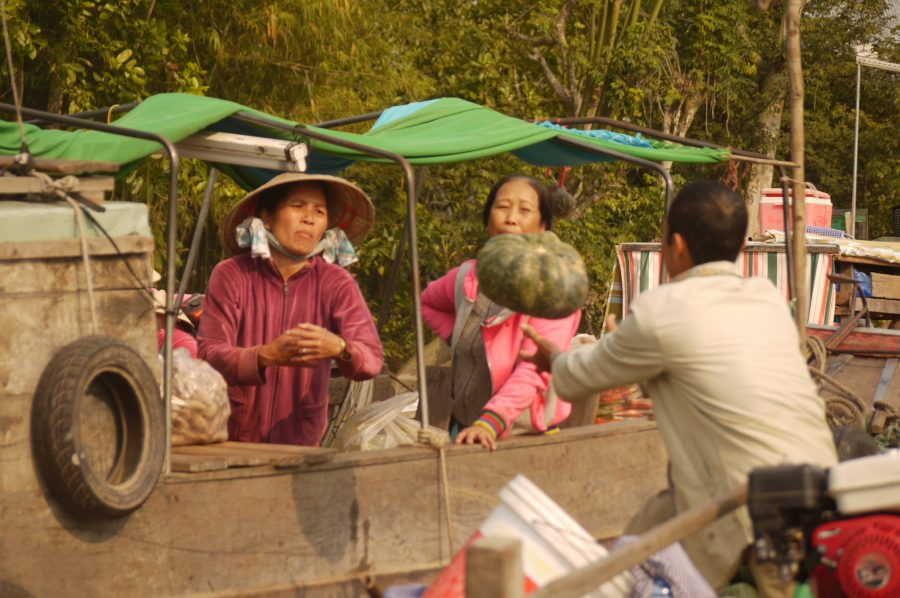 Tossing pumpkins from boat to boat at the floating markets