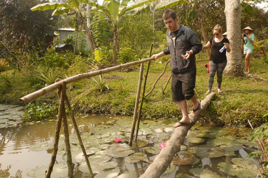 Michael and Noelle crossing a simple bridge inside the fruit garden