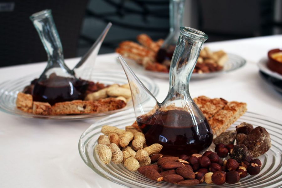 Traditional Spanish Porron Filled With Desert Wine, Served With Nuts