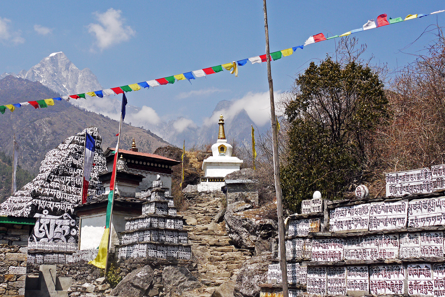 Buddhist Mantras painted on stones with prayer flags flying overhead