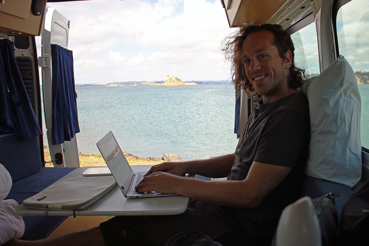 How we afford to travel full-time, Catching up on freelance work in the back of our camper in New Zealand