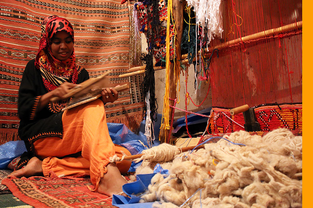 Berber girl weaving carpets by hand.
