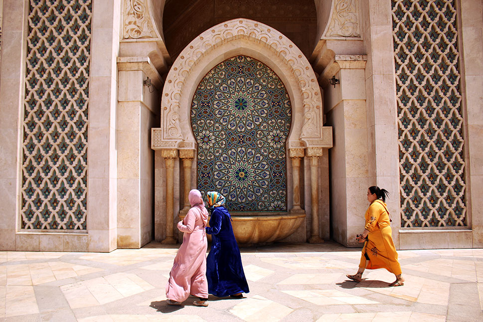 Local women walking past one of the 41 fountains at the Grande Mosquée Hassan II, Casablanca.