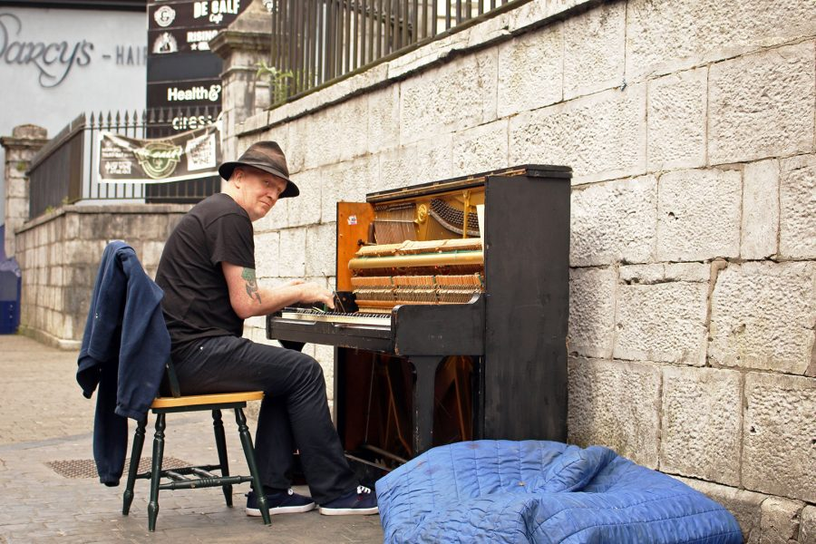 A Busker plays the piano on the streets of Cork