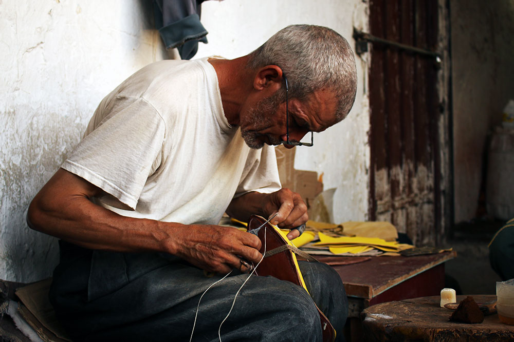 Stitching Balgha, traditional Moroccan leather shoes.