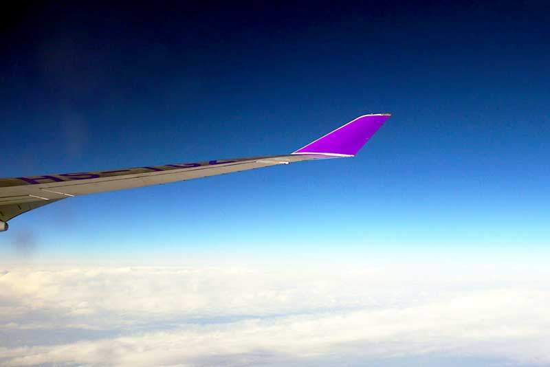 Air Travel in India - view of wing of an airplane in a blue sky