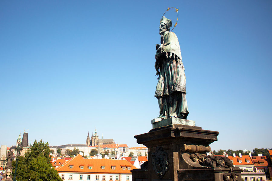 The statue of St. John of Nepomuk on Charles Bridge with Prague castle in the background, one of the Best Free Things To Do In Prague, what to see in Prague, Prague on a budget