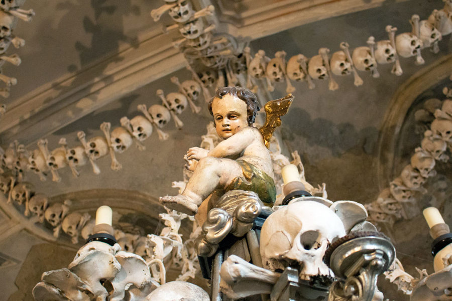 A cheerful cherub sits atop a candelabra of skulls and bones | Sedlec Ossuary