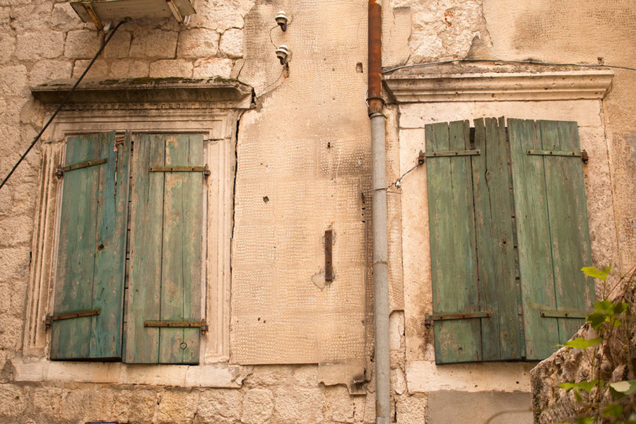 Green window shutters stand out against the stone buildings | Kotor's Old Town
